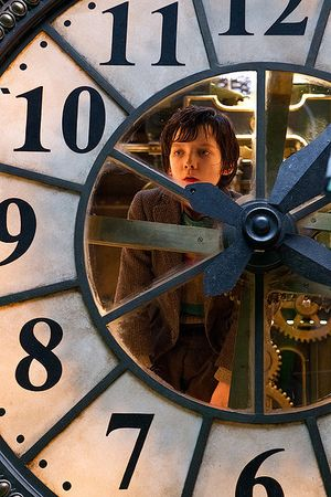 Hugo looking out a clock
